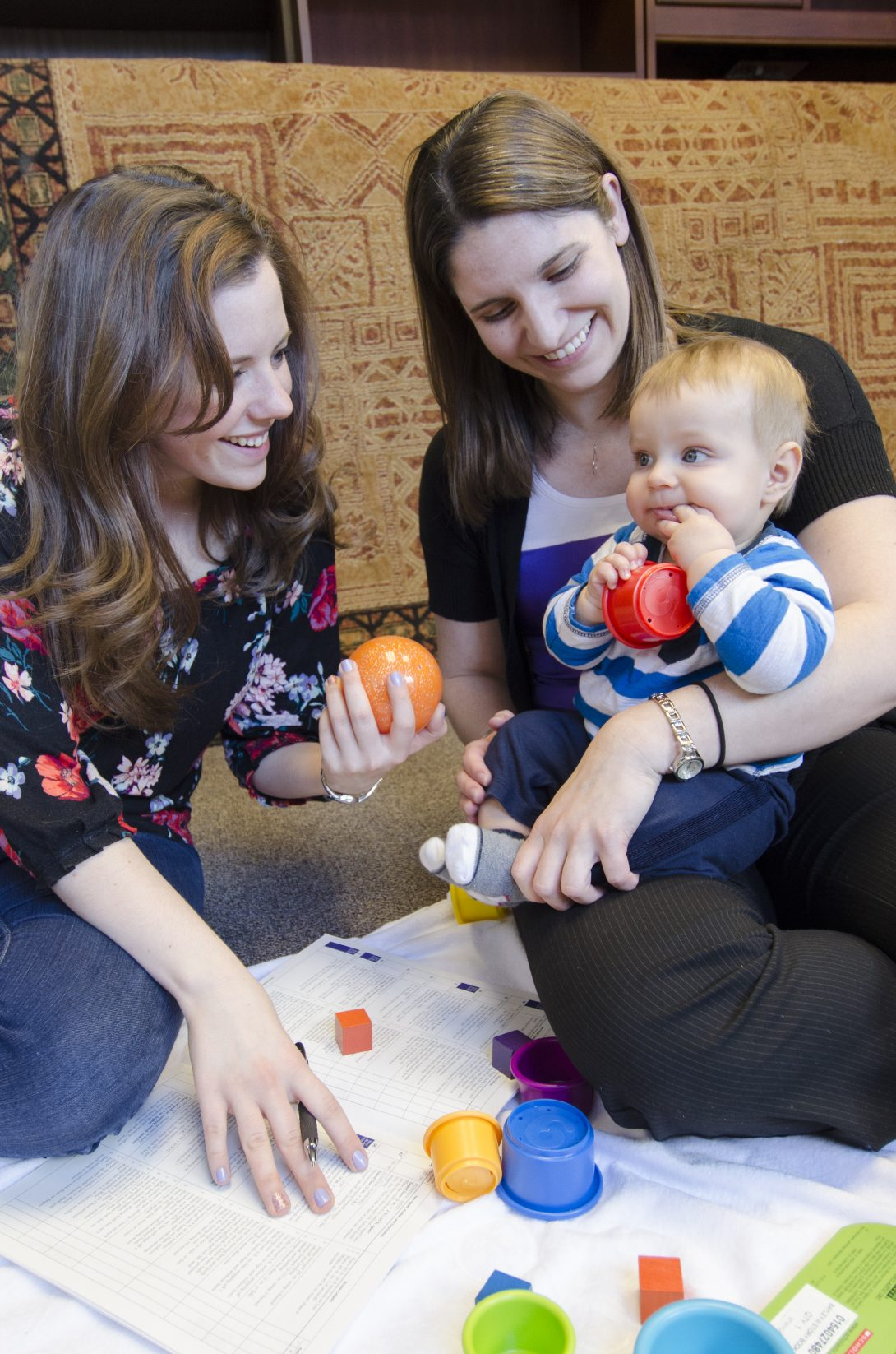 Two women playing with a baby with colored blocks
